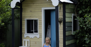 Lucinda outside the cubby her dad built