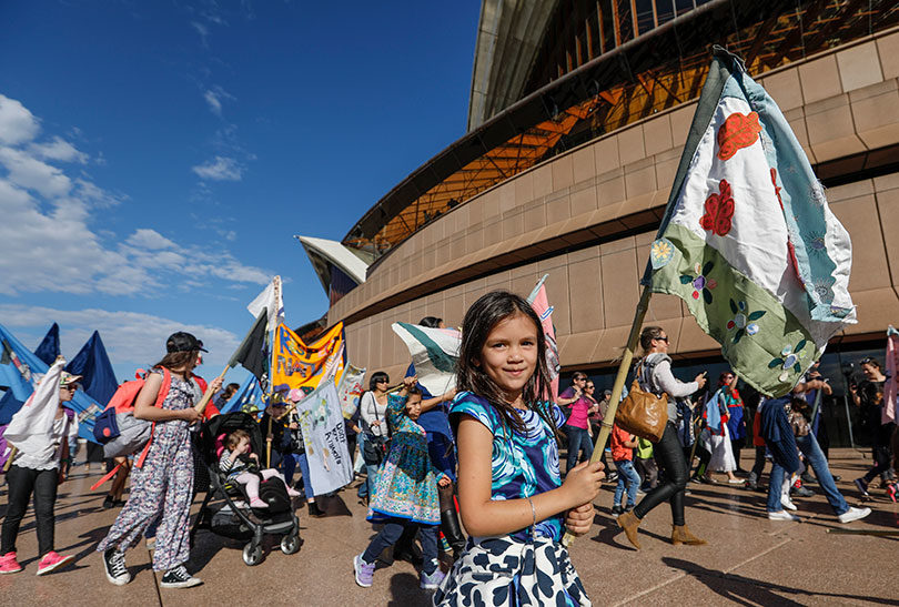 Kids with the flags they made for the parade for the Children's Republic of Sydney at the Opera House. Photo: Dallas Kilponen