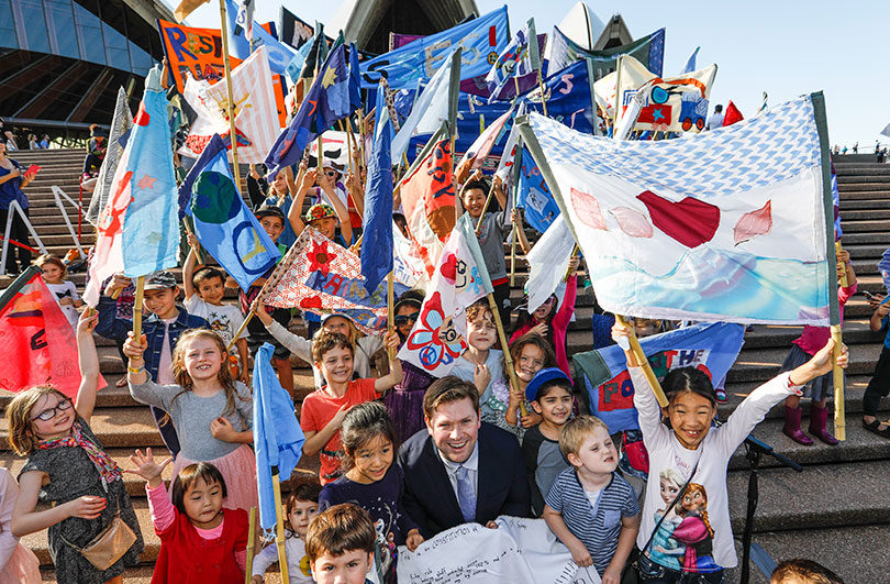NSW Liberal politician Scott Farlow with kids and their specially made flags after the Children's Republic of Sydney parade at the Opera House. Photo: Dallas Kilponen