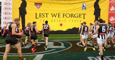 The players walk to the Anzac banner during the round four AFL match between the Essendon Bombers and the Collingwood Magpies at Melbourne Cricket Ground on April 25, 2015. Photo: Michael Dodge, AFL Media, Getty Images