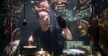 A member of the Between Music band performing with a custom-made drum kit in a glass water tank ahead of the AquaSonic underwater concert in Aarhus, Denmark. Photo: Jonathan Nackstrand, AFP