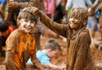 Brother and sister Tom, 9, and Evie Barnard, 7, getting drenched from head to toe at the mud pit at the Festival of Mud in Adelaide. Photo: James Elsby