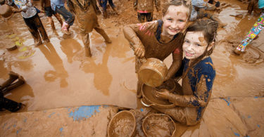 Friends Amelia Reid, left, and Matilda Lehman made mud pies together in the mud pit at the Festival of Mud in Adelaide. Photo: James Elsby