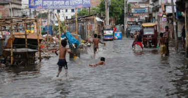 Boys in Dhaka, the capital of Bangladesh, playing in a polluted, water-logged street on the way to collect drinking water on June 17, 2017. Photo: Mehedi Hasan, NurPhoto, AFP