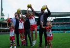 From left, Siarra Bolton, Jordan Davis, and Taya and Leni O'Loughlin and their dads Jude Bolton, Nick Davis and Michael O'Loughlin celebrate the news Sydney Swans have set up a youth girls academy. Photo: Sydney Swans