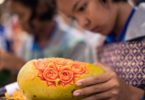 A Thai girl carves flower patterns into a papaya during a fruit and vegetable carving competition in Bangkok on August 4, 2017. Photo: Roberto Schmidt, AFP