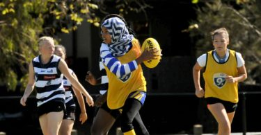 Amren Abrahim, 12, playing in her blue and white striped hijab. Photo: North Melbourne Football Club