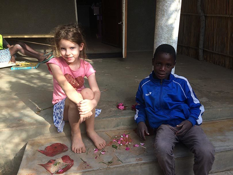 Amelia with Francisco on the front steps of the orphanage where Sam and Amelia lived for two years in Mozambique.