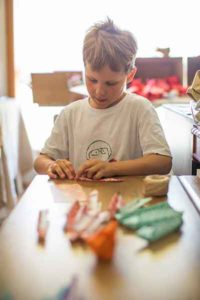 Agustin Candusso, 8, works on his paper-folding art work. Photo: Jack of Hearts Photography