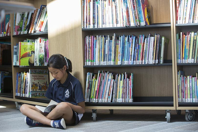 Emmy Zhou, 9, reading at Realm public library in Ringwood, Victoria. Photo: Elizabeth Clancy