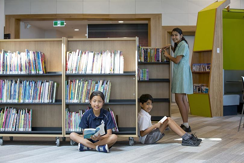 From left, Emmy Zhou 9, Hamish Billimoria, 9, and Dhiya Billimoria, 12, reading at Realm public library in Ringwood, Victoria. Photo: Elizabeth Clancy