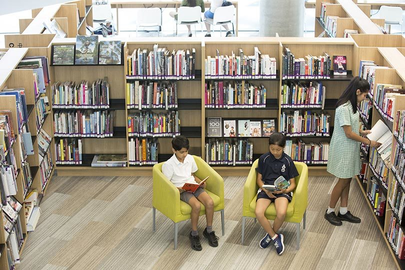 From left, Hamish Billimoria, 9, Emmy Zhou, 9, and Dhiya Billimoria, 12, reading at Realm public library in Ringwood, Victoria. Photo: Elizabeth Clancy